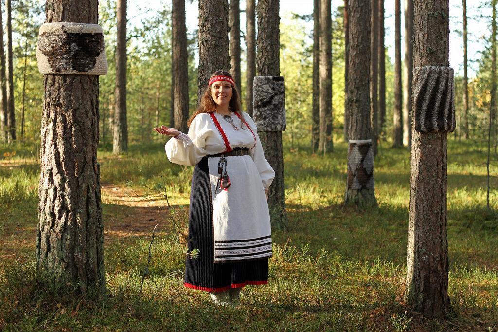 Jenni Vanhanen metsässä ryijyjen ympäröimänä
